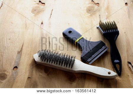 Set of Wire Brushes on Wooden Background