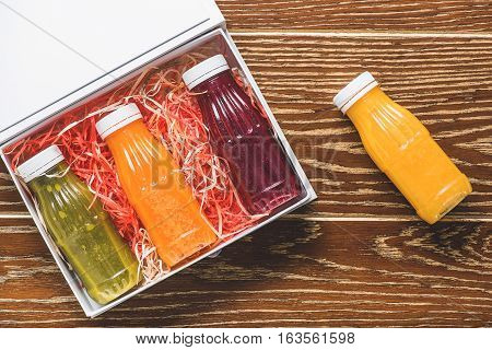 Plastic flacks with different colourfull juices are in open box at table. One yellow beverage in volume is on wooden surface