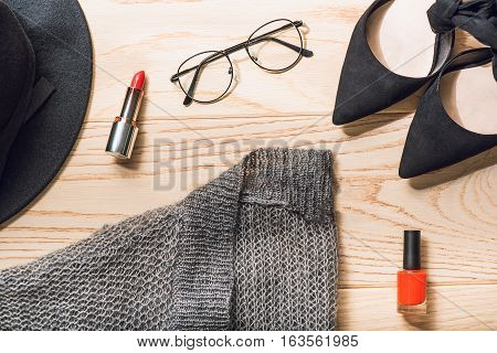Black shoes and hat beside red lipstick, scarlet nail polish are on wooden surface.