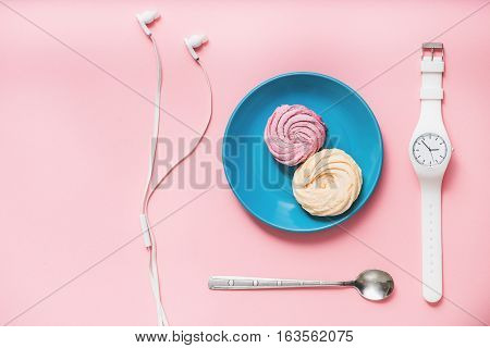 Small blue plate with sweet zephyrs near white wristwatch and dessert spoon on bright pink surface. Earphones beside utensil. Top view