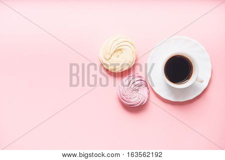 Small white cup of black beverage at round plate near two swirled cakes. Top view