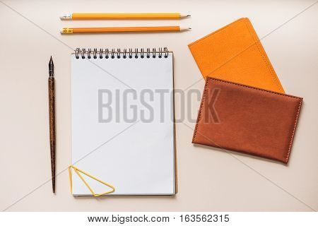 Open notebook with yellow clip, business card holders and pencils on isolated area