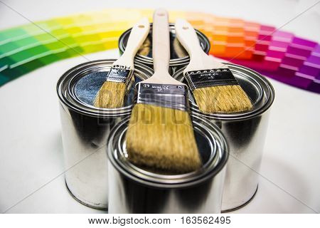 Painting, paint brushes on a color cans on a white surface, decorative painting concept. Paint colors in metal cans with color samples in background, three painting brushes ready for painter to paint walls in the house.