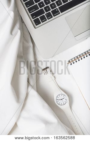 White wristwatch is nearby open notebook. Drapery textile beside computer. Top view