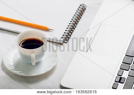 Small mug with black bracing beverage is nearby open laptop and notebook