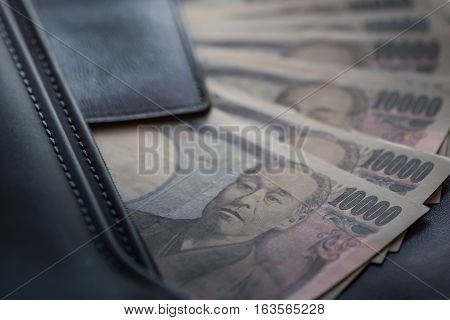 Close up of ten thousand yen banknote call ichiman banknote in japan inside black business leather bag for traveler.