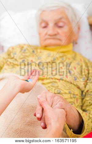 Photo of elderly woman taking the medication