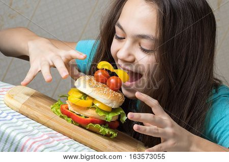 Portrait of a 11 year old girl a hamburger-eating as a smiley face with tomatoes eyes