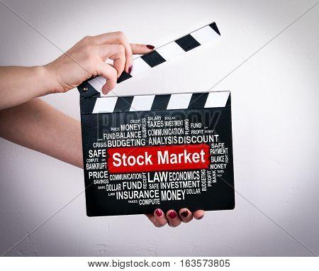 Stock Market Concept. Female hands holding movie clapper.