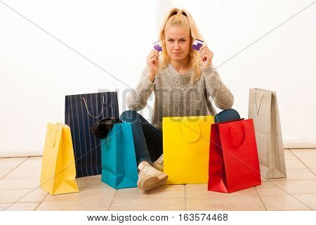 angry young woman with bags siting on flor afetr shopping
