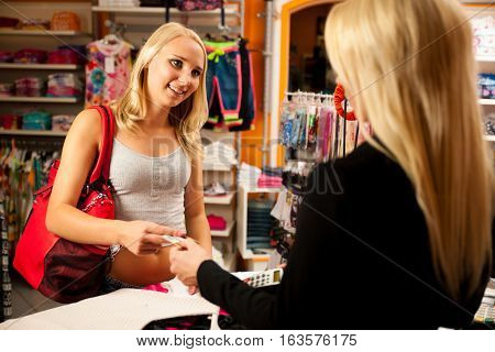 Woman Paying After Purchase In Clothing Store