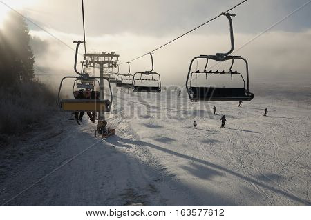 Winter mountains panorama with ski slopes and ski lifts sunny day with fog and sun rays