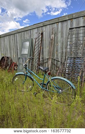 An old retro girl's bike is parked in a junkyard where items lean against a weathered wood fence.