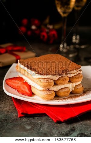 Tiramisu with strawberry and glasses of champagne on the table. Valentines concept. Dark moody style.