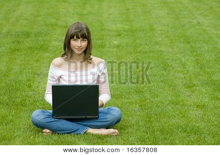 Teenager surfing internet on the grass