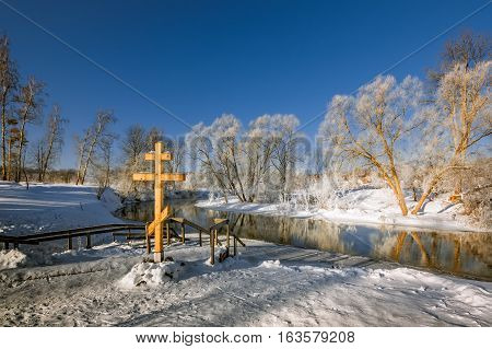 Christian cross on the coast of the winter river in the morning