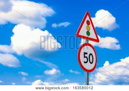 two road signs speed limit and traffic light on a background of blue sky and clouds