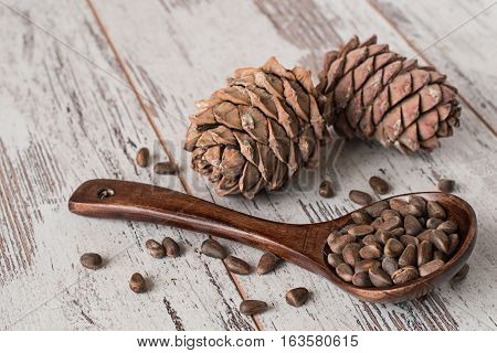 Wooden spoons with pine nuts and pine cones on an old table.