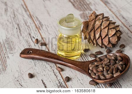 Cedar cones, oil in a glass bottle and cedar nuts in a wooden spoon on the old table.