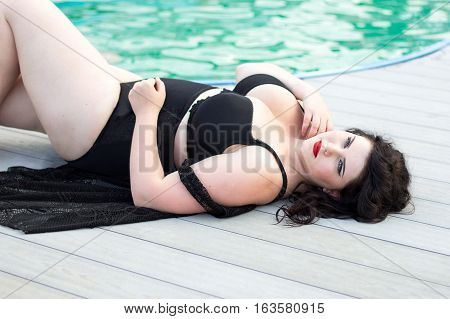Young beautiful busty curvy plus size model with big breast in black bra xxl woman professional makeup and hairstyle lying by the pool