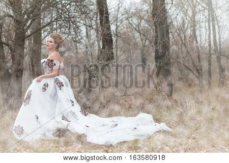 Beautiful young lady in gorgeous vintage white dress in the forest in the fog professional makeup and hairstyle. Late autumn cold. Melancholy.