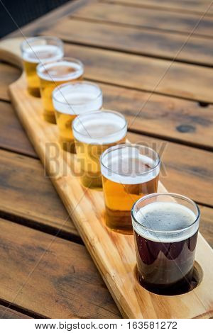 Beer samplers in small glasses individually placed in a hole fashioned into a unique wooden tray.
