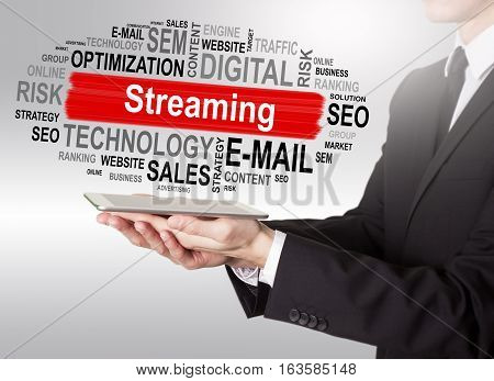 Streaming concept, young man holding a tablet computer.