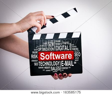 Software concept. Female hands holding movie clapper.