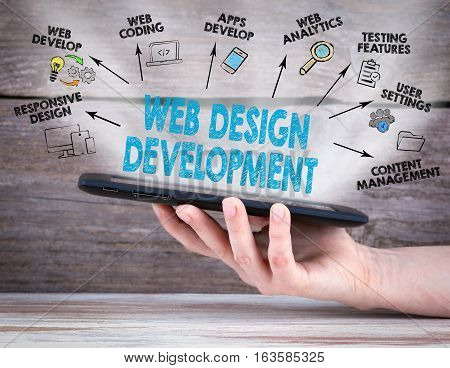 Web Design and Development concept. Tablet computer in the hand. Old wooden background.
