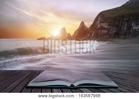 Stunning Dramatic Sunrise Over Beach With Jagged Rocks Coastline Coming Out Of Pages Of Book