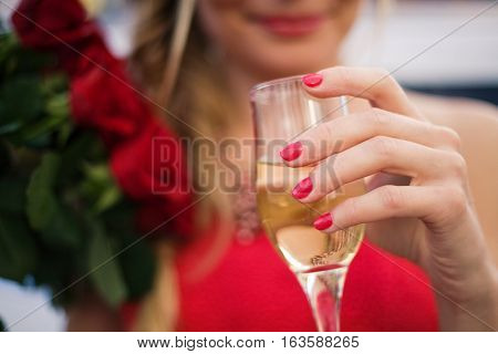 Young woman holding glass of champagne and bouquet of roses