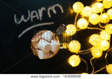 Word warm on  blackboard with Hot cocoa in Glass and big marshmallows and yellow lights on black background