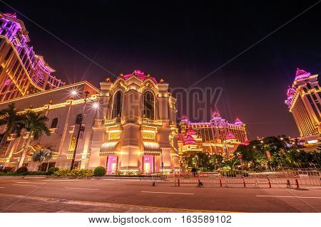 Macau, China - December 8, 2016: scenic view of pink and gold colors of Galaxy Macau Casino hotel in Cotai Strip, during the laser show. Macao typical street scene of nightlife.