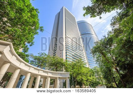 Colonnade in Hong Kong Park with skyline of modern skyscrapers and towers on background. Central business district in Hong Kong Island. Beautiful sunny day with blue sky.