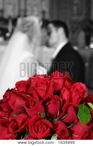 Wedding Couple Kissing Behind Bridal Bouquet