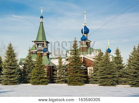 Fancy wooden church with blue domes and bell tower