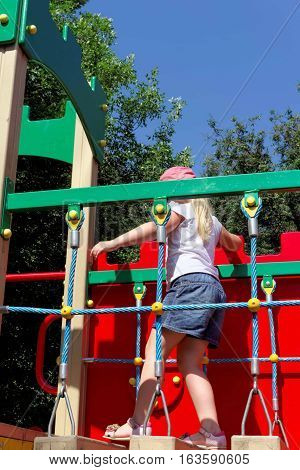 Girl 6 years goes by hanging a horizontal ladder on the playground