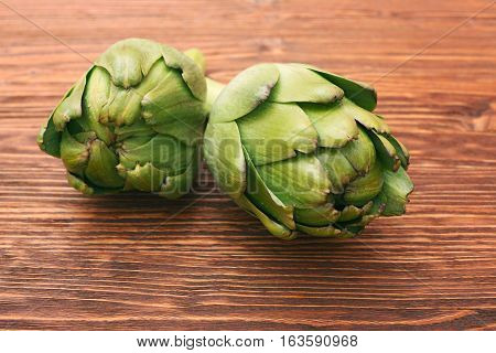 Ripe Organic Artichokes on the rustic wooden board