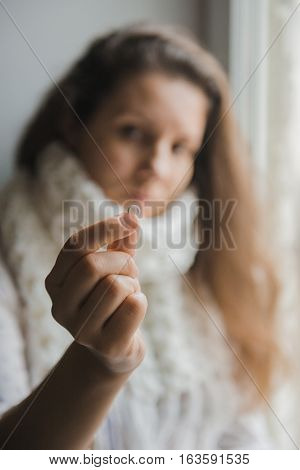 Ill young girl. A girl sitting at home near the window and holds the tablet in hands. Sick woman holding pill in hand.