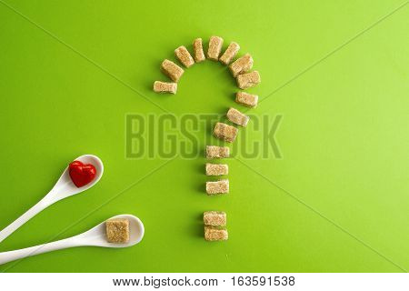 Brown sugar cubes shaped as a question mark on greenery background and two white spoons with heart on one of them. . Top view. Diet unhealty sweet addiction diabet concept