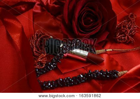 items for creating female attraction, red lipstick and jewelry on a red background