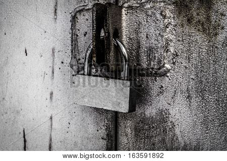 Padlock, new metal padlock on gray background, grunge padlock, metal door
