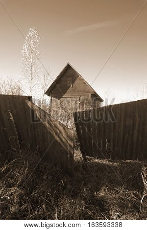 Abandoned uninhabited house in countryside. Genre photography, sepia style