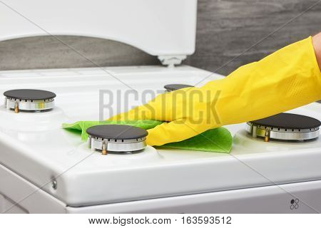 Woman's hand in yellow rubber protective glove cleaning white gas stove with green rag on gray background poster