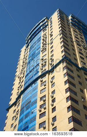 High yellow modern multi-storey building building on blue cloudless sky vertical view