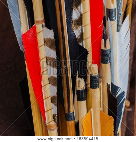 Closeup Medieval set of old wooden arrows with bright plumage, square background