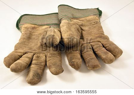 Pair of well used gloves isolated on white.