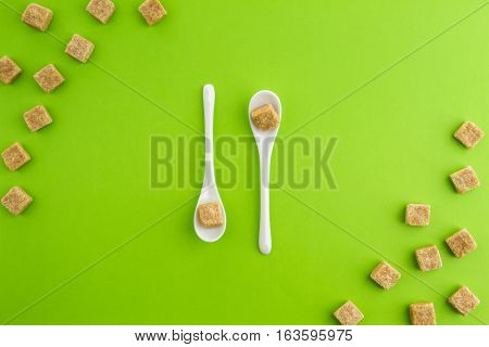 Brown sugar cubes on greenery background with two white teaspoons in the middle. Top view. Copy space for text. Diet unhealty sweet addiction concept