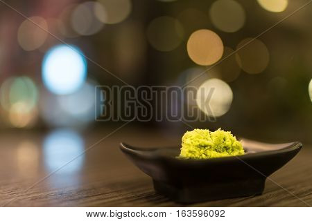 Wasabi in black saucer on wooden table with depth of field effect Japanese food's condiment bokeh background