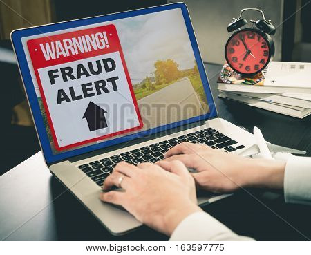 Business Fraud Alert on Computer Screen in office.